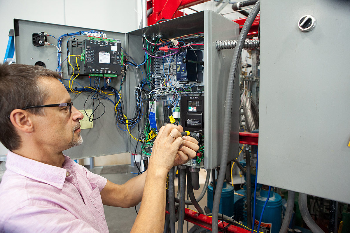 OxEon engineer working on the electrical panel for the Syngas production skid.