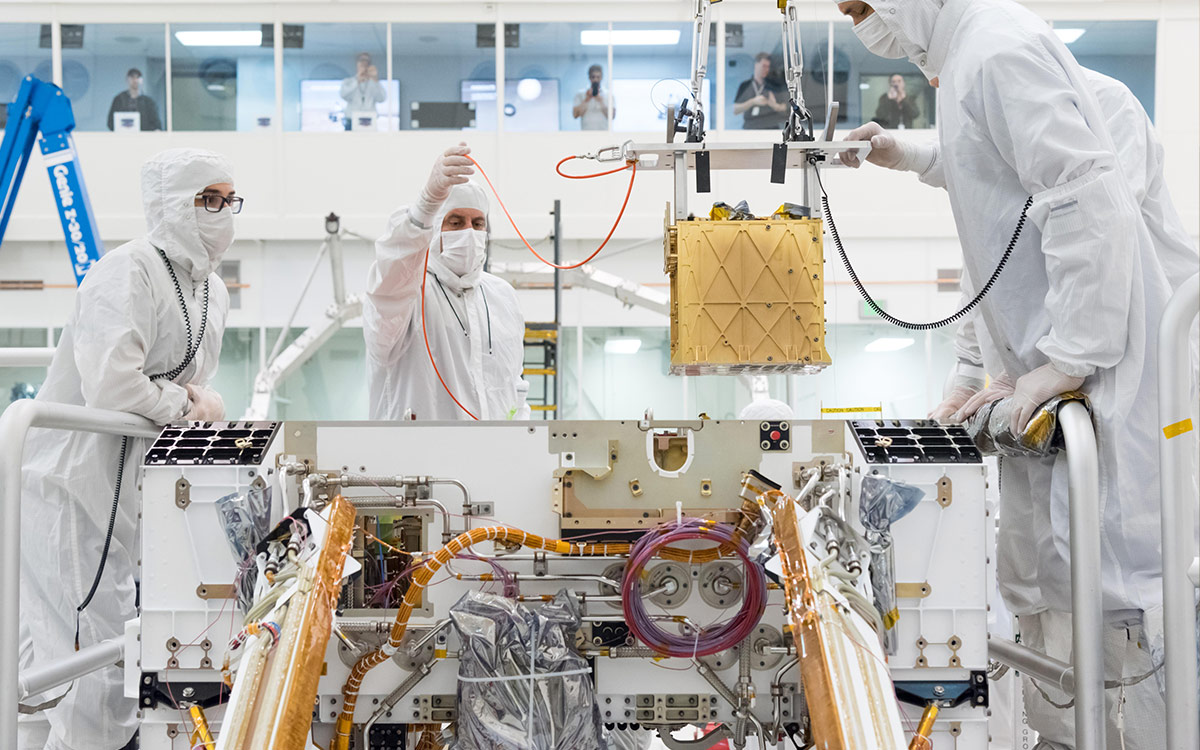 Technicians in the clean room are carefully lowering the Mars Oxygen In-Situ Resource Utilization Experiment (MOXIE) instrument into the belly of the Perseverance rover. Credit: NASA/JPL-Caltech